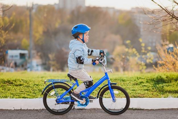 Il ragazzino con il casco va in bicicletta in una giornata di sole