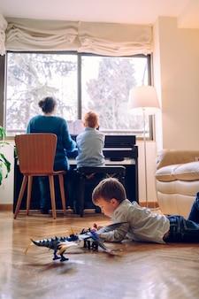 Ragazzino che gioca sul pavimento del salotto con i giocattoli di dinosauro. attività infantili e di apprendimento. lo stile di vita familiare trascorre del tempo insieme. bambini con virtù musicali e curiosità artistica.
