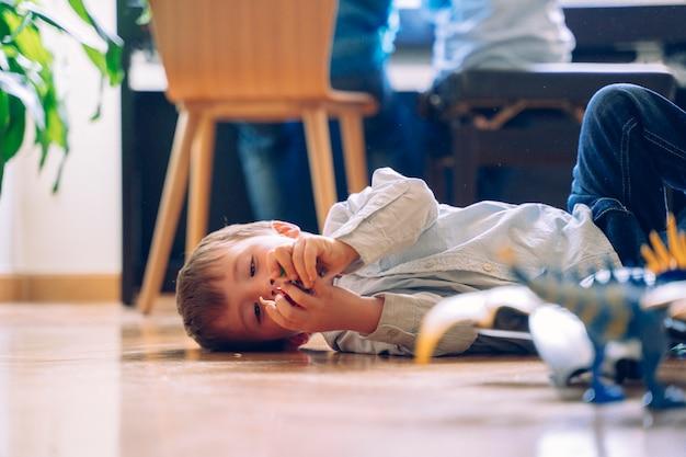 Ragazzino che gioca sul pavimento di casa con giocattoli nuovi di zecca