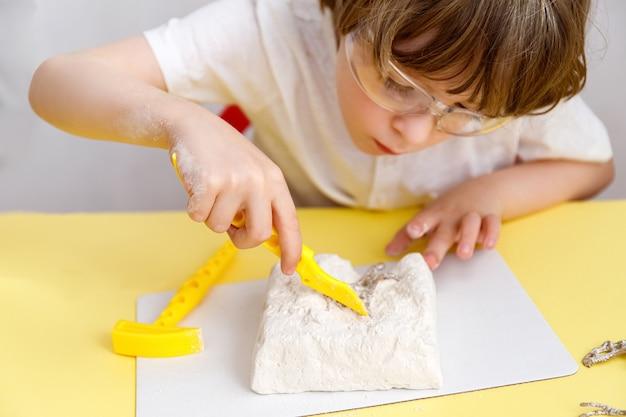 Ragazzino che gioca con l'insieme di archeologia del giocattolo. bambino che utilizza strumenti in un sito di scavo archeologico