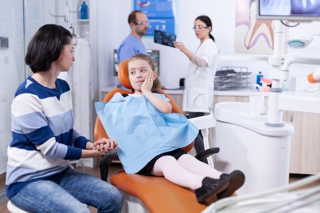 Ragazzino con espressione dolorosa che tocca il viso durante il trattamento dentale professionale. bambino con sua madre durante il controllo dei denti con stomatolog seduto su una sedia.