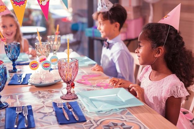 Bambini piccoli che partecipano a una festa di compleanno e si siedono al tavolo