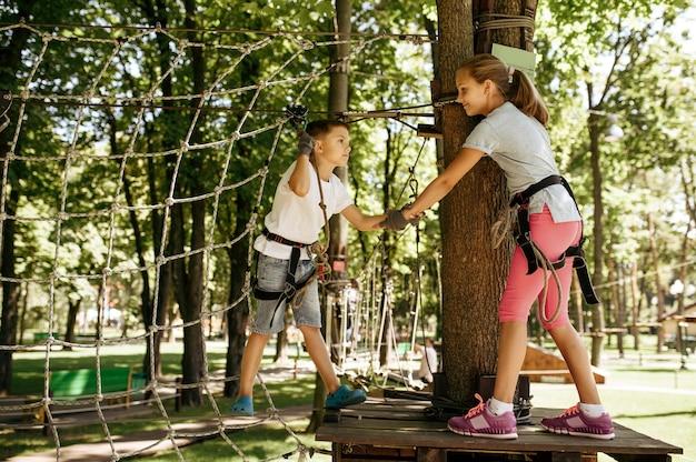 I bambini piccoli si arrampicano sulla rete nel parco avventura
