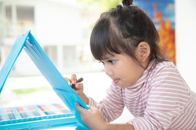 I bambini piccoli che disegnano con una matita colorata sono una buona attività per migliorare l'arte creativa e le abilità di scrittura a mano nei bambini. immagine concettuale per l'hobby dell'istruzione e dell'apprendimento.