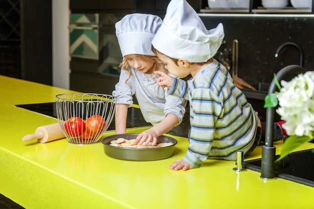 Ragazzini ragazza e ragazzo con cappello da chef che preparano cuocere la torta di mele fatta in casa in cucina. fratello e sorella che cucinano cibo sano a casa e si divertono. infanzia, famiglia, concetto di aiuto del lavoro di squadra