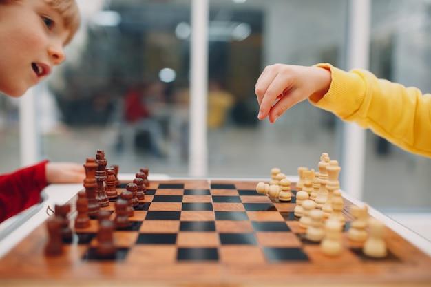 Bambini piccoli che giocano a scacchi all'asilo o alla scuola elementare. gioco di scacchi per bambini.