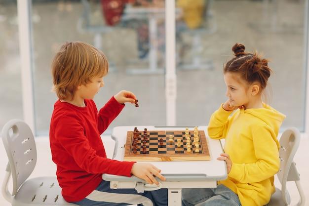 Bambini piccoli che giocano a scacchi all'asilo o alla scuola elementare giocano a scacchi per bambini