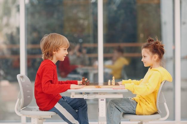 Bambini piccoli che giocano a scacchi all'asilo o alla scuola elementare