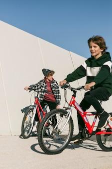 Bambini piccoli che guidano insieme le loro biciclette all'aperto