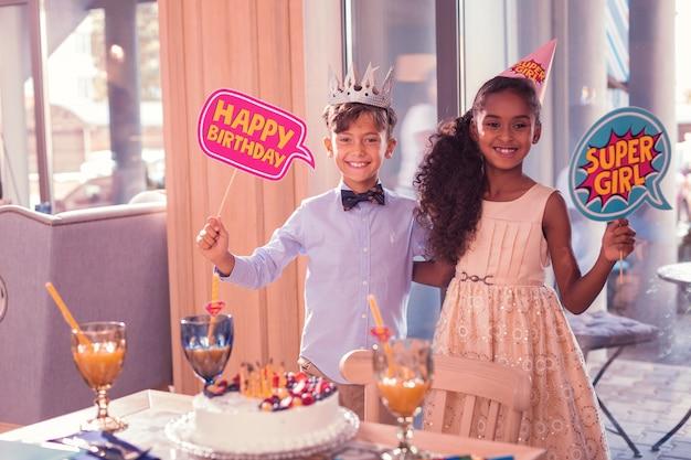 Bambini piccoli sorridenti e tenendo il segno di buon compleanno
