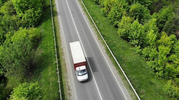 Piccolo camion che guida in autostrada, aerea. erba verde e alberi su entrambi i lati della strada.