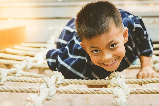 Piccolo bel ragazzo straniero sorride arrampicata su corda, giocando con divertimento e felice