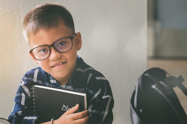 Piccolo studente straniero adorabile, ragazzo che tiene il manuale sorride con divertimento, felice a scuola.