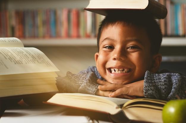Piccolo studente straniero adorabile, ragazzo che impara, gioca con divertimento, felice in classe.