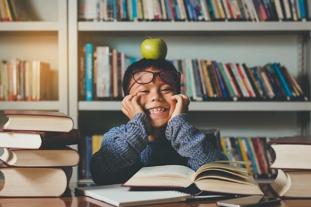 Piccolo studente straniero adorabile, ragazzo che impara divertendosi, felice in classe.