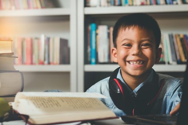 Piccolo adorabile studente straniero che impara in biblioteca con divertimento e felicità