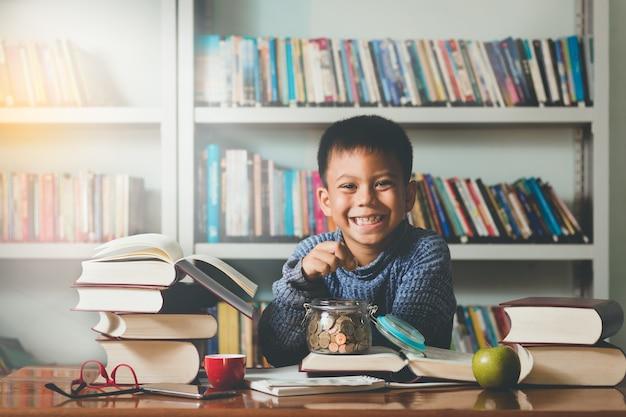 Sorrisi di studente adorabile del piccolo straniero che tengono le monete dei soldi che imparano con il divertimento.