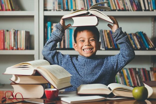 Piccolo adorabile studente straniero sorride imparando, giocando con divertimento e felicità.