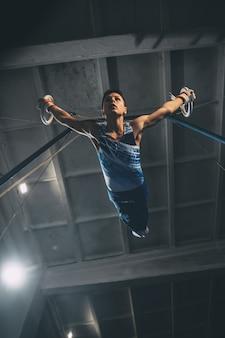 Piccolo ginnasta maschio che si allena in palestra, composto e attivo. ragazzino in forma caucasica, atleta in abbigliamento sportivo che pratica esercizi per forza, equilibrio. movimento, azione, movimento, concetto dinamico Foto Premium