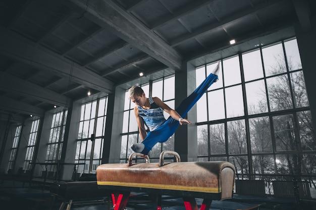 Piccolo ginnasta maschio che si allena in palestra, composto e attivo.