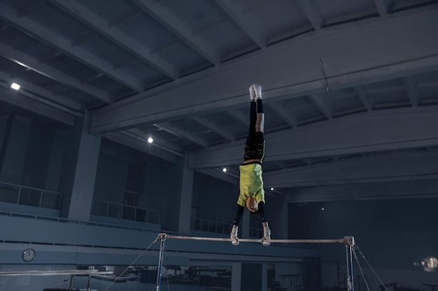 Piccolo ginnasta maschio che si allena in palestra, flessibile e attivo. ragazzino in forma caucasica, atleta in abbigliamento sportivo che pratica esercizi per forza, equilibrio. movimento, azione, movimento, concetto dinamico.