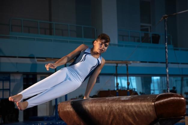 Piccola ginnasta maschio allenamento in palestra flessibile e attiva