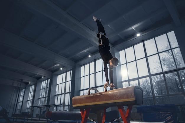Piccolo ginnasta maschio che si allena in palestra flessibile e attivo