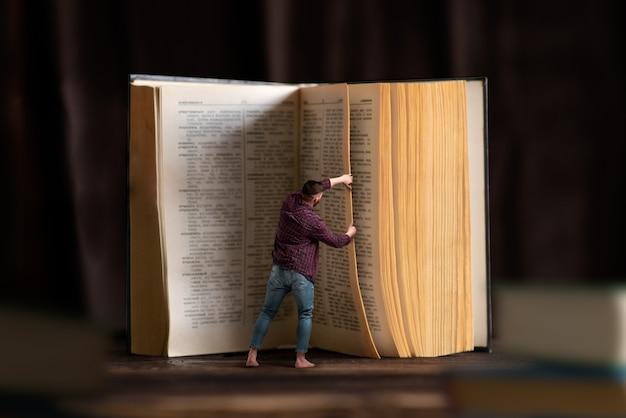 Omino gira la pagina di un grande libro, effetto scala. acquisire conoscenza e istruzione, leggere il concetto.