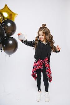 La piccola ragazza moderna dei pantaloni a vita bassa in vestiti alla moda e baloons, fa la pace con la sua mano. autoscatto. scatta foto al telefono