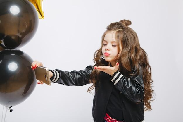 Bambina moderna hipster in abiti alla moda e baloons, selfie, bacio. scatta foto al telefono
