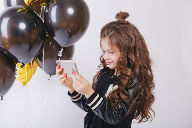 Piccola ragazza moderna dei pantaloni a vita bassa in vestiti e baloons di modo, selfie. scatta foto al telefono