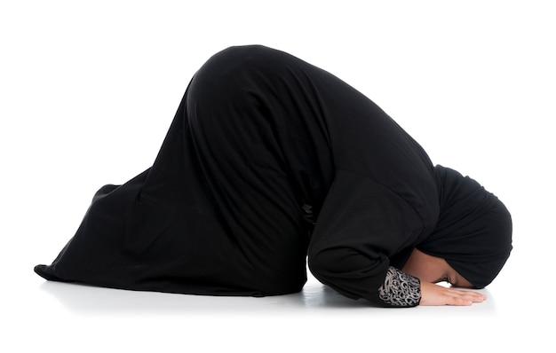 Bambina musulmana che prega in un costume tradizionale