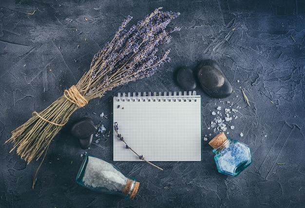 Piccolo taccuino, lavanda, sale marino minerale e pietre zen su pietra grigia. vista dall'alto.