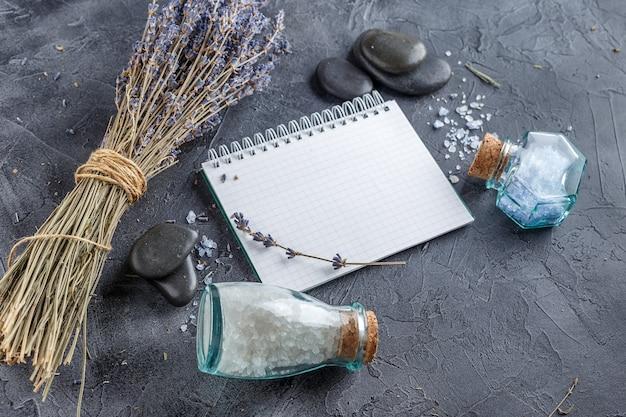 Piccolo taccuino, lavanda, sale marino minerale e pietre zen su pietra grigia.