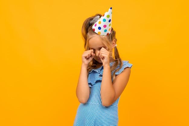 Il piccolo bambino offeso piange sul giallo per il suo compleanno