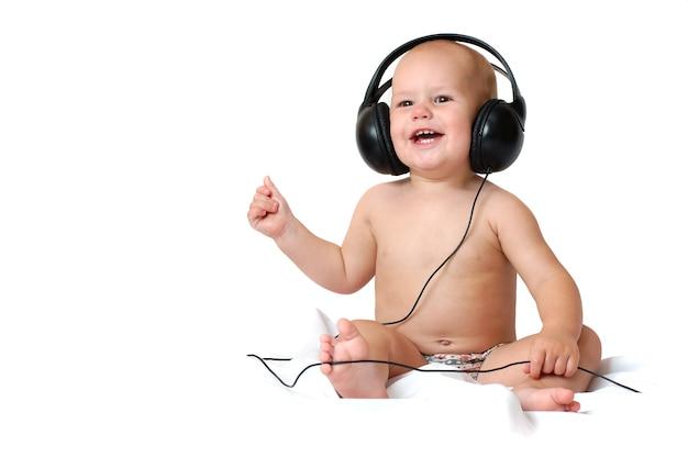 Un ragazzino di un anno ascolta musica in grandi cuffie e sorride su uno sfondo bianco isolato