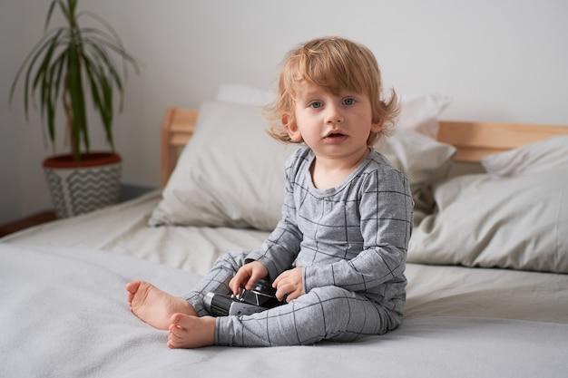 Un bambino di un anno che gioca sul letto con una vecchia macchina fotografica, foto di stile di vita