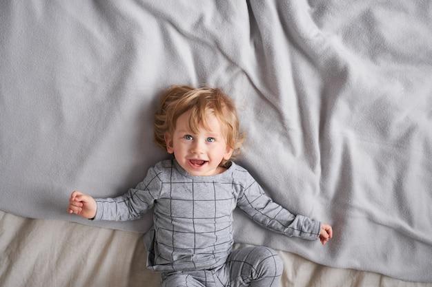 Un bambino di un anno che gioca e si diverte sul letto di casa, foto di stile di vita