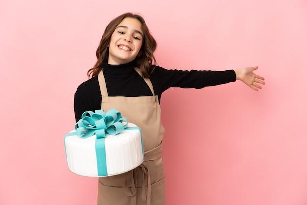 Piccolo pasticcere che tiene una grande torta isolata su fondo rosa che estende le mani a lato per invitare a venire