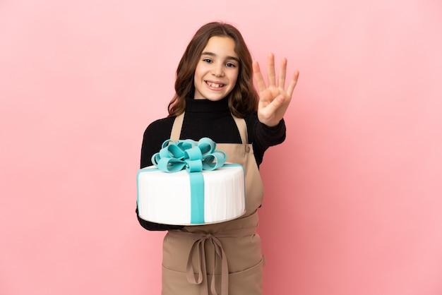 Piccolo pasticcere che tiene una grande torta isolata su sfondo rosa felice e conta quattro con le dita