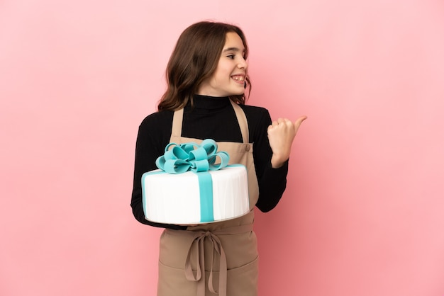 Piccolo pasticcere che tiene una grande torta isolata su sfondo rosa che punta al lato per presentare un prodotto