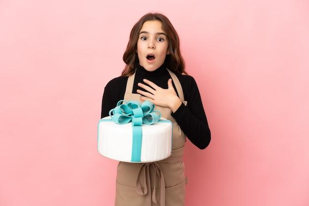 Piccolo pasticcere che tiene una grande torta isolata su sfondo rosa sorpreso e scioccato mentre guarda a destra
