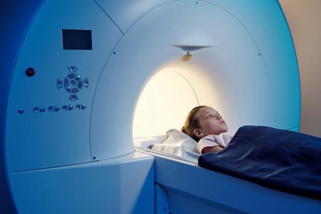 Piccolo paziente sotto un asciugamano blu sdraiato sul lungo tavolo della macchina per la risonanza magnetica