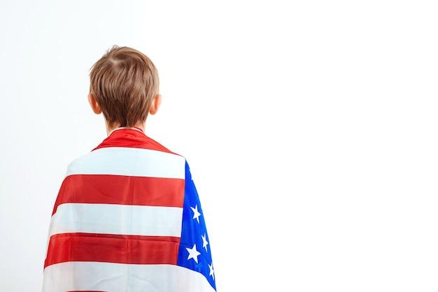 Piccolo patriota con bandiera americana, vista posteriore. il bambino felice tiene una bandiera dell'america. concetto di giorno di indipendenza.
