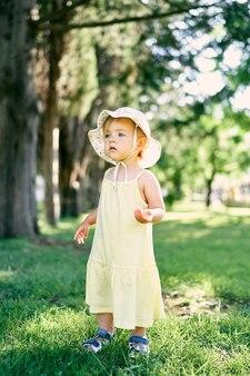 La piccola ragazza pensierosa in un cappello di panama sta sull'erba verde nel parco