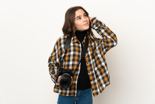 Piccola ragazza fotografa isolata sullo sfondo che ha dubbi e pensa
