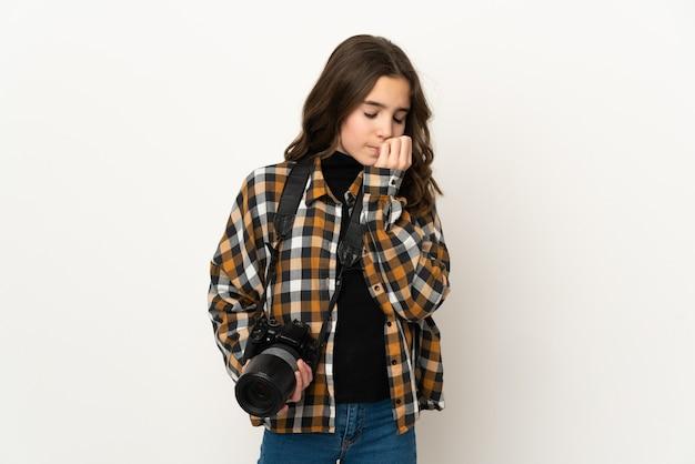 Piccola ragazza del fotografo isolata su fondo che ha dubbi