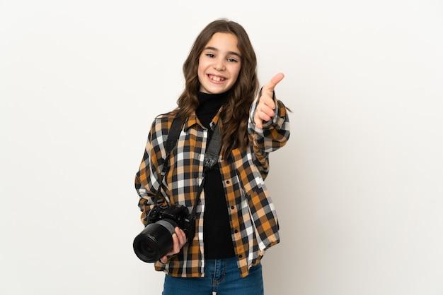 Piccola ragazza del fotografo isolata su priorità bassa che stringe la mano per chiudere un buon affare