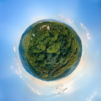 Piccolo globo del pianeta con colline montuose scure ricoperte di pini misti verdi e boschi lussureggianti circondati da un cielo azzurro e limpido con nuvole bianche.