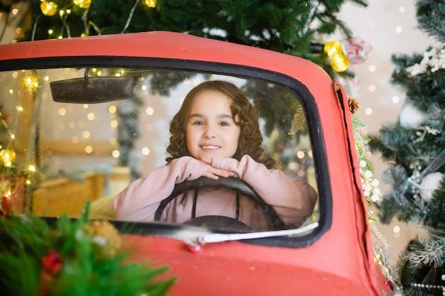 Piccola ragazza in età prescolare seduta dietro il volante in un'auto rossa di carta decorativa su sfondo magico con abete e luci di natale e capodanno